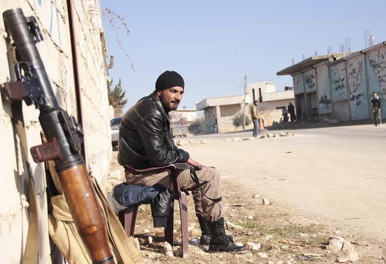 A rebel fighter guards a street to prevent members of the al Qaeda-affiliated Islamic State of Iraq and the Levant (ISIL) from entering Jabal al-Zawiya in Idlib January 6, 2014. REUTERS/Fadi Mashan