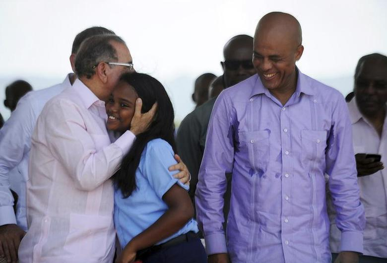 Presidents of the Dominican Republic, Danilo Medina (L), and of Haiti, Michel Martelly (R), greet a student as they visit a nursery to inaugurate a reforestation program for Hispaniola Island which both countries share, in the border town of Juana Mendez, June 5, 2013. REUTERS/Ricardo Rojas