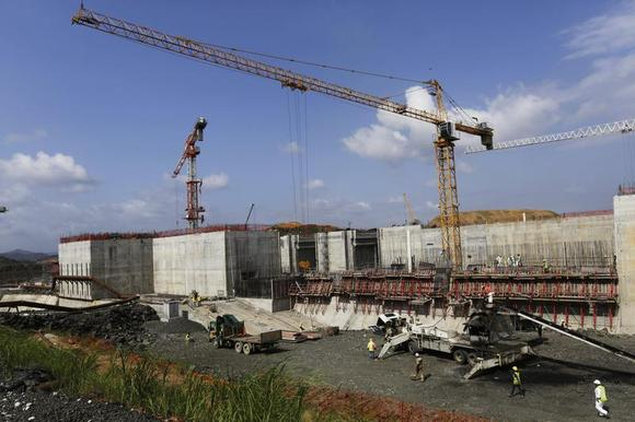 Cranes are seen next to workers at the construction site of the Panama Canal Expansion project during an organized tour for the media on the Pacific side at the outskirts of Panama City January 4, 2014. REUTERS/Carlos Jasso
