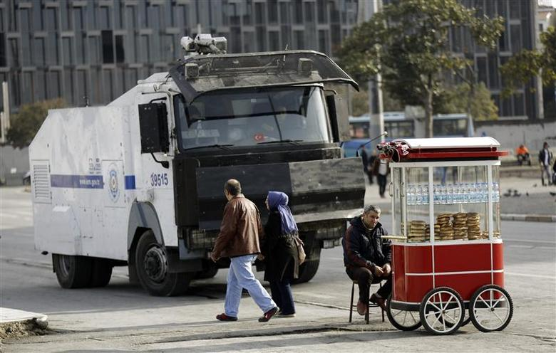 Pedestrians walk past by an armoured police vehicle at Taksim square in central Istanbul January 6, 2014. REUTERS/Murad Sezer