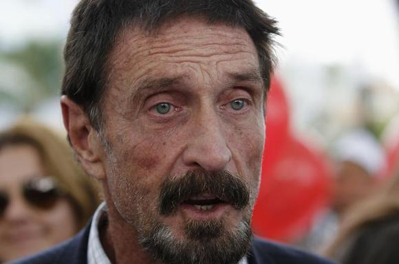 Computer software pioneer John McAfee speaks with reporters outside his hotel in Miami Beach, Florida December 13, 2012. REUTERS/Joe Skipper/Files