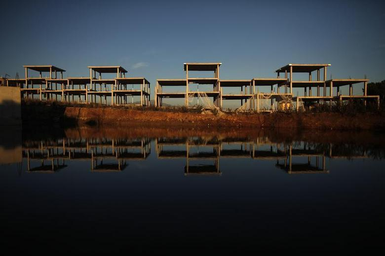 An unfinished residential building is reflected in a pool of water in Marbella, near Malaga, southern Spain January 31, 2012. REUTERS/Jon Nazca