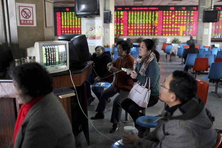 Investors look at computer screens showing stock information at a brokerage house in Shanghai, January 2, 2014. REUTERS/Aly Song