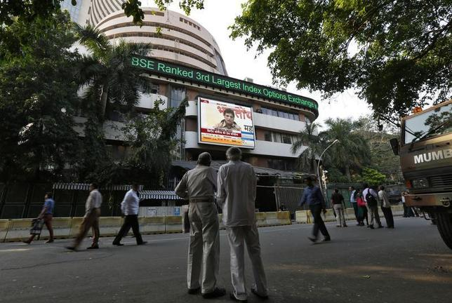People watch a large screen displaying India's benchmark share index on the facade of the Bombay Stock Exchange (BSE) building in Mumbai December 9, 2013. REUTERS/Mansi Thapliyal