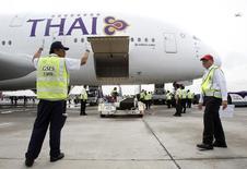 Equipe de solo da Thai Airways trabalha perto do primeiro Airbus Thai A380-800 conforme ele chega ao aeroporto internacional Suvarnabhumi em Bangcoc. A companhia aérea nacional Thai Airways International disse nesta terça-feira que espera retornar à lucratividade em 2014 após sofrer enormes prejuízos nos primeiros nove meses do ano passado. 29/09/2012 REUTERS/Chaiwat Subprasom