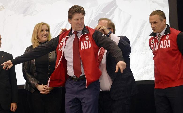 Canada's Men's Olympic Ice Hockey Team executive director Steve Yzerman (R) and Minister of Transport Lisa Raitt (L) look on as head coach Mike Babcock (C) dons a team jacket during a news conference in Toronto January 7, 2014. REUTERS/Aaron Harris