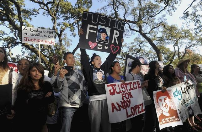 Vanessa Lopez, 15, holds a placard (in black) as she joins hundreds of protesters at Santa Rosa Junior College demanding justice for Andy Lopez Cruz in Santa Rosa, California October 29, 2013. REUTERS/Noah Berger