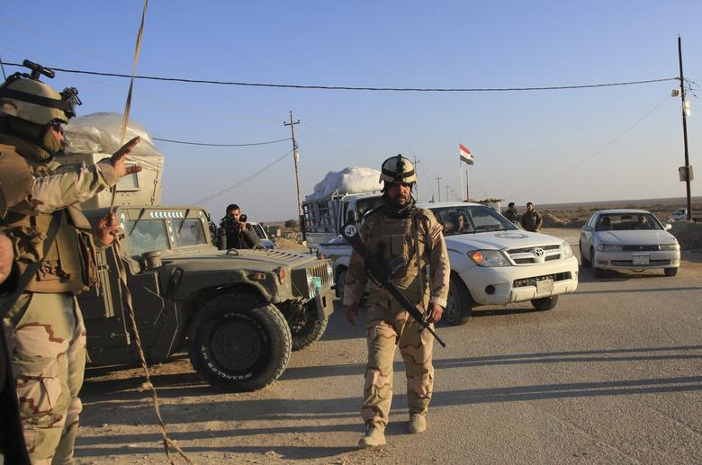 Iraqi soldiers stand guard at a checkpoint in Ein Tamarm, a town some 40 km (25 miles) west of Kerbala, January 7, 2014. REUTERS/Mushtaq Muhammed