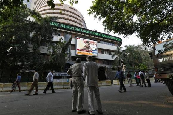 People watch a large screen displaying India's benchmark share index on the facade of the Bombay Stock Exchange (BSE) building in Mumbai December 9, 2013. REUTERS/Mansi Thapliyal/Files