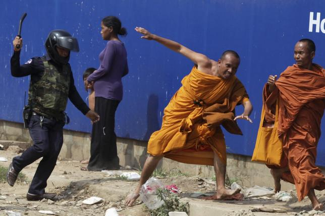 A security guard chases away Buddhist monks from a camp occupied by anti-government demonstrators in Phnom Penh January 4, 2014. REUTERS/stringer