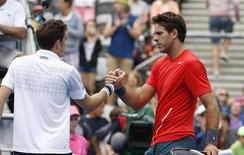 Juan Martin Del Potro of Argentina (R) meets France's Nicolas Mahut of France at the net following his second round men's singles win at the Sydney International tennis tournament in Sydney, January 8, 2014. REUTERS/Jason Reed