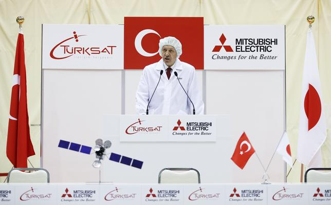 Turkey's Prime Minister Tayyip Erdogan, wearing a dust-free garment, delivers a speech during a ceremony to mark the shipment of the Turksat-4A satellite at Mitsubishi Electric Corp's Kamakura Works, the satellite production facility, in Kamakura, south of Tokyo January 8, 2014. REUTERS/Issei Kato