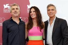 """U.S. actor George Clooney (R) poses with actress Sandra Bullock (C) and director Alfonso Cuaron during a photocall at the 70th Venice Film Festival in Venice August 28, 2013. Clooney and Bullock star in Alfonso Cuaron's movie """"Gravity"""", which debuts at the festival. O suspense espacial """"Gravidade"""" recebeu 11 indicações ao Bafta nesta quarta-feira, colocando o filme em vantagem na principal premiação do cinema britânica, enquanto """"12 Anos de Escravidão"""" e """"Trapaça"""" foram nomeados em 10 categorias. """"Gravidade"""", que estrela os ganhadores do Oscar Sandra Bullock e George Clooney, foi nomeado em categorias como melhor filme, melhor atriz, melhor diretor para Alfonso Cuarón, melhor som e efeitos visuais, e destaque do cinema britânico. REUTERS/Alessandro Bianchi"""