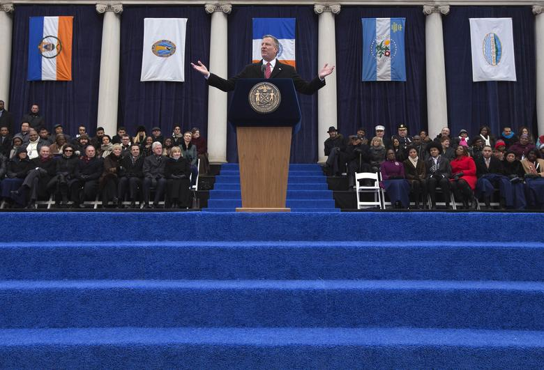 New York City Mayor Bill de Blasio, flanked by the flags of the five city boroughs, makes a speech during his inauguration ceremony on the steps of City Hall in New York on January 1, 2014. REUTERS/Adrees Latif