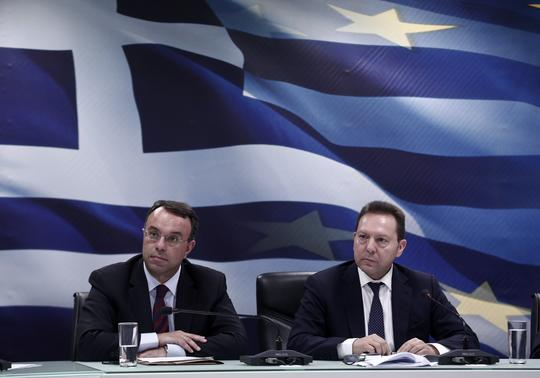 Greece's Finance Minister Yannis Stournaras (R) and Deputy Finance Minister Christos Staikouras listen to questions during a news briefing related to the Greek presidency of the European Union in Athens January 7, 2014. REUTERS-Yorgos Karahalis