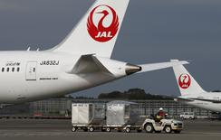 A airport worker drives a luggage transport vehicle past one of the company's Boeing Co's 787 Dreamliner plane (L) and a Beoing 767 at Narita international airport in Narita, east of Tokyo, November 11, 2013. REUTERS/Toru Hanai
