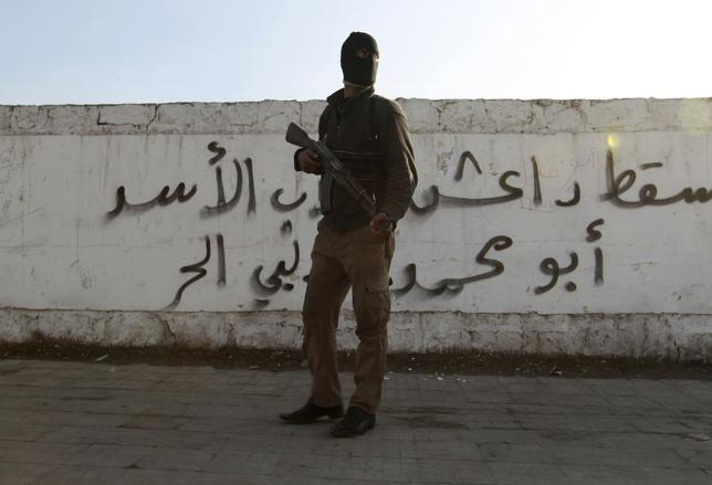 A Free Syrian Army fighter carries his weapon as he stands in front of graffiti that reads ''Daesh (Islamic State of Iraq and the Levant ) down'' at Masaken Hanano neighborhood in Aleppo January 7, 2014. REUTERS/Jalal Alhalabi