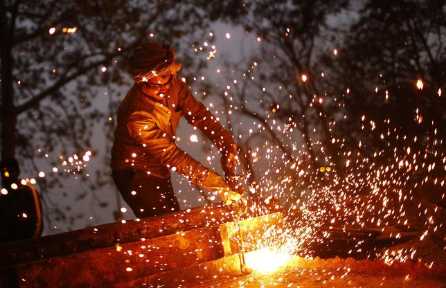 A worker uses a welding torch to weld an iron machine at the construction site of a flyover in New Delhi January 6, 2014. REUTERS/Anindito Mukherjee