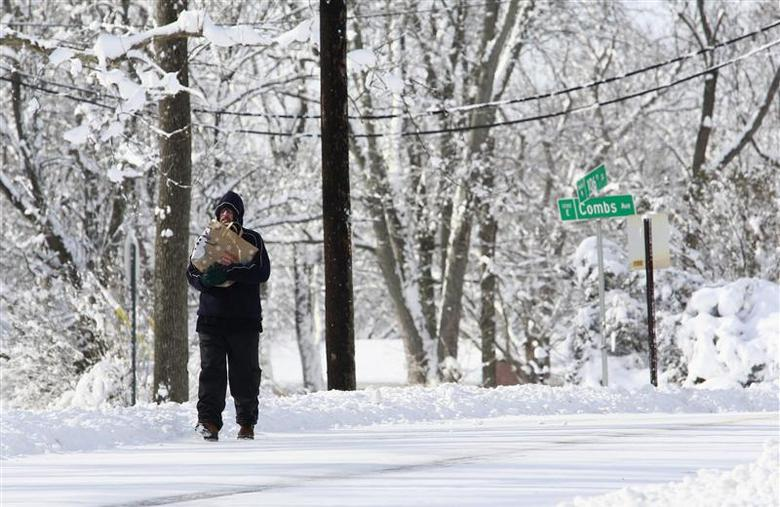 John Perry walks down the street with supplies to see if he has power at his home in Indianapolis, Indiana, January 6, 2014. REUTERS/Brent Smith