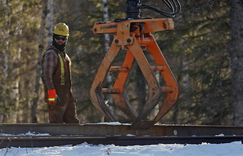 A CN worker looks on while working on the railway in Plaster Rock, New Brunswick, January 8, 2014. REUTERS/Mathieu Belanger