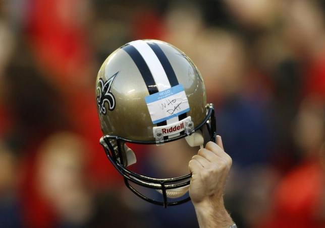 A member of the New Orleans Saints staff holds up a helmet during the NFL's Super Bowl XLIV football game against the Indianapolis Colts in Miami, Florida, February 7, 2010. REUTERS/Carlos Barria