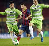 Barcelona's Lionel Messi (C) fights for the ball against Getafe's Juan Rodriguez (L) and Pedro Leon during their Spanish King's Cup match at Camp Nou stadium in Barcelona January 8, 2014. REUTERS/Albert Gea