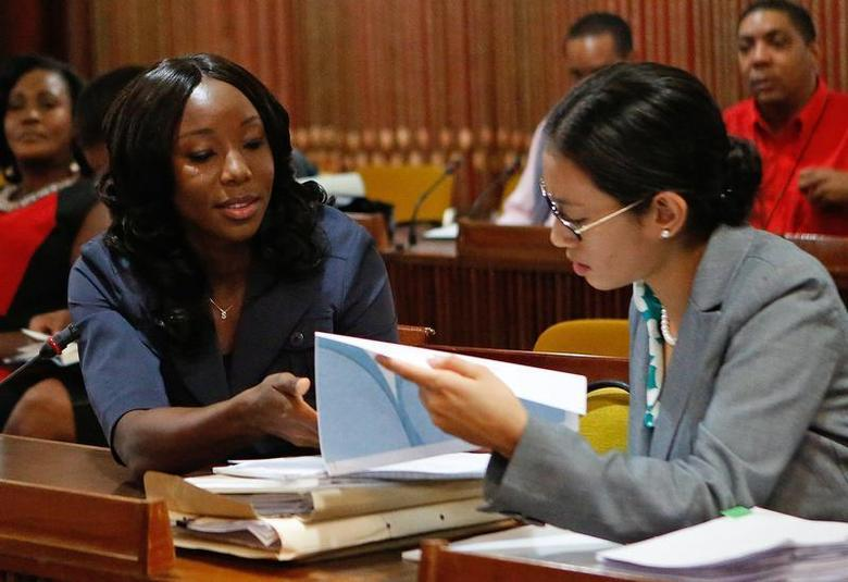Jamaica's Olympic sprinter Sherone Simpson (L), who tested positive for doping at the Jamaican Championships in 2013, talks with her attorney Danielle Chai during the second day of her hearing before the country's anti-doping commission in Kingston January 8, 2014. REUTERS/Gilbert Bellamy