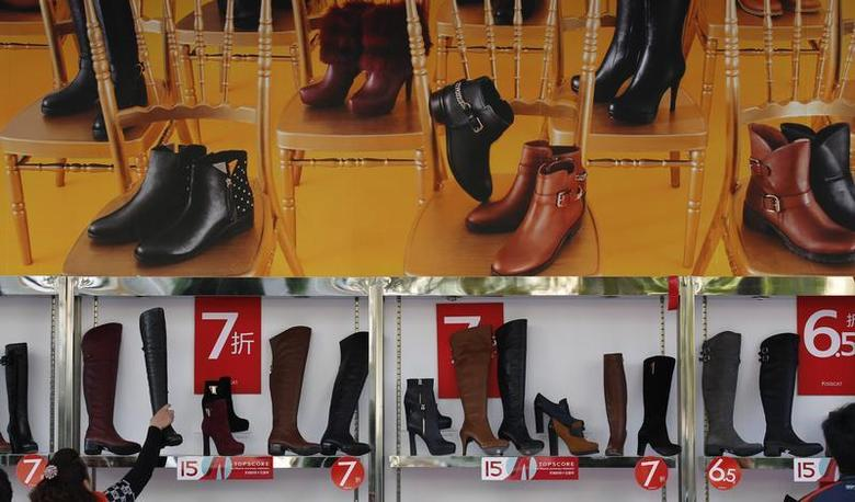 A customer picks up a shoe at a shop where posters advertising price discounts are hung, outside a department store in Beijing, October 23, 2013.REUTERS/Kim Kyung-Hoon