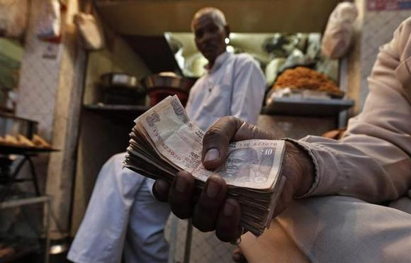 A street side restaurant owner holds a bundle of currency notes as he sits outside his restaurant in New Delhi November 22, 2013. REUTERS/Adnan Abidi/Files