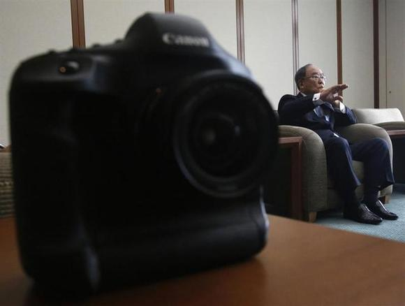 Canon Inc Chairman and CEO Fujio Mitarai speaks next to the company's digital SLR camera EOS-1D X during an interview with Reuters at the company's headquarters in Tokyo January 9, 2014. REUTERS/Yuya Shino