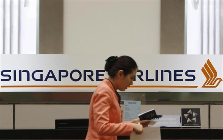 A staff member walks by a Singapore Airlines (SIA) logo at a ticketing counter at Changi airport in Singapore May 14, 2013. REUTERS/Edgar Su/Files