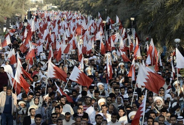 Anti-government protesters carrying Bahraini flags and photos of Shi'ite scholar Isa Qassim march during an anti-government rally organized by main opposition group al-Wefaq in Budaiya, west of Manama, January 3, 2014. REUTERS/Stringer