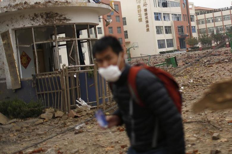 A man wears a mask while walking past a debris-covered basketball court of a school a day after an explosion at a Sinopec Corp oil pipeline in Huangdao, Qingdao, Shandong Province November 23, 2013. REUTERS/Aly Song