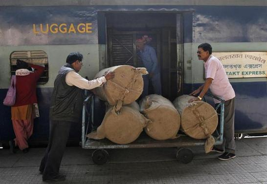 Porters transport goods on a hand-pulled trolley to load on a train at a railway station in Kolkata January 8, 2014. REUTERS/Rupak De Chowdhuri