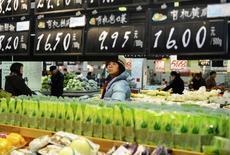 Cliente olha para etiquetas de preços de vegetais orgânicos em supermercado em Hangzhou, na província de Zhejiang, 9 de janeiro de 2014. A inflação anual ao consumidor da China desacelerou com mais força do que o esperado em dezembro para 2,5 por cento, a mínima em sete meses, aliviando os temores do mercado de aperto da política monetária embora o banco central esteja pisando no freio da liquidez bancária. 09/01/2014 REUTERS/China Daily