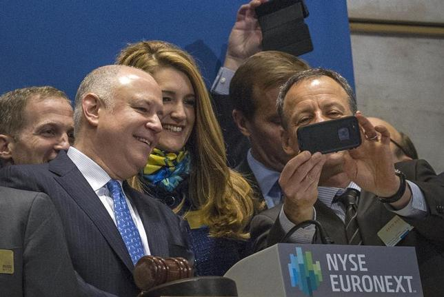 Intercontinentalexchange Chairman and CEO Jeffrey Sprecher (L), his wife Kelly Loeffler, ICE Vice President of Corporate Affairs, and ICE Chief Strategy Officer David Goone look at a mobile phone on the bell podium of the New York Stock Exchange, November 18, 2013.REUTERS/Brendan McDermid