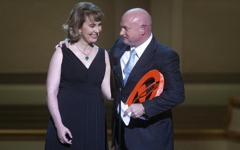 Gabrielle Giffords is hugged by her husband Mark Kelly during the Glamour Magazine Women of the Year event in New York, November 11, 2013. REUTERS/Carlo Allegri