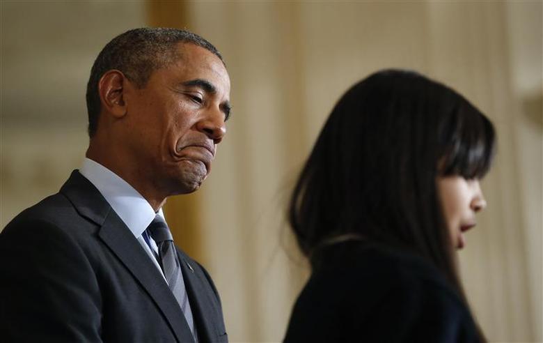 U.S. President Barack Obama listens to Kiara Molina, of Harlem, NY, introduce him to speak at the White House in Washington January 9, 2014. REUTERS/Kevin Lamarque