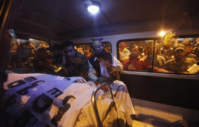 Relatives of Pakistan's Crime Investigation Department (CID) Chief Chaudhry Aslam sit in an ambulance with his body outside Jinnah Postgraduate Medical Centre in Karachi January 9, 2014. REUTERS/Akhtar Soomro