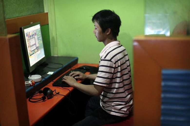 A man plays an online game in an internet cafe in downtown Shanghai August 6, 2009. REUTERS/ Nir Elias/Files