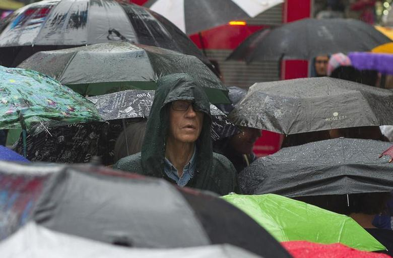 A man stands among umbrellas in the line for Broadway show tickets in New York June 10, 2013. REUTERS/Zoran Milich