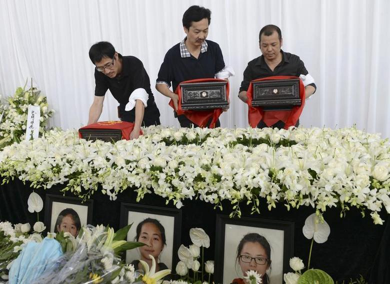 The fathers of Liu Yipeng, Wang Linjia and Ye Mengyuan, the three girls who died in the Asiana Airlines crash, carry the ashes of their daughters during a memorial in Jiangshan, Zhejiang province, August 1, 2013. REUTERS/Stringer