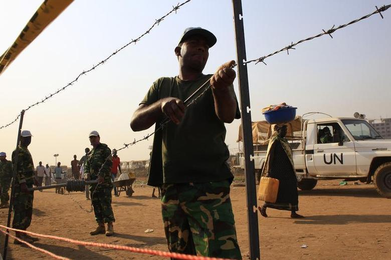 United Nations Mission in South Sudan (UNMISS) personnel erect barbed wire fencing around Tomping camp, where some 15,000 people who fled their homes following recent fighting are sheltered by the United Nations, in Juba January 7, 2014. REUTERS/James Akena