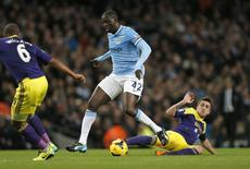 Manchester City's Yaya Toure (C) is challenged by Swansea's Pablo Hernandez during their English Premier League soccer match at the Etihad stadium in Manchester, northern England December 1, 2013. REUTERS/Phil Noble