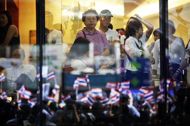 People look on from inside a shopping mall as thousands protest against the amnesty bill in Bangkok's central business district in this November 6, 2013 file photo. REUTERS/Damir Sagolj/Files