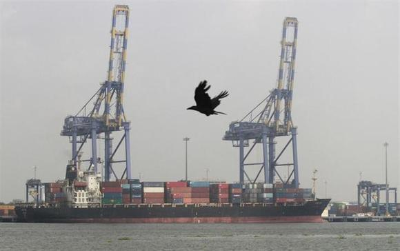 A crow flies past a container ship docked at a port in Vallarpadam in Kochi December 11, 2013. REUTERS/Sivaram V/Files