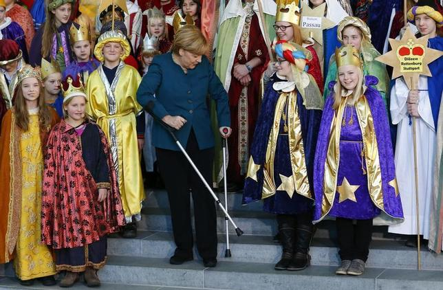 German Chancellor Angela Merkel stands with the aid of crutches as she meets carols singers (Sternsinger) during a reception at the Chancellery in Berlin, January 7, 2014. REUTERS/Tobias Schwarz