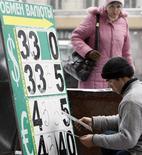Мужчина меняет вывеску пункта обмена валюты в Москве 16 января 2009 года. Рубль ушел в минус к бивалютной корзине и её компонентам на дневных торгах пятницы - участники рынка отмечают локальный корпоративный спрос на валюту, перебивающий продажи экспортной выручки. REUTERS/Denis Sinyakov