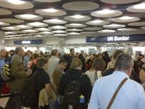 Travellers queue to be processed by UK Border Agency immigration control officers at Heathrow airport's Terminal 5 in London May 20, 2012. Picture taken May 20, 2012. REUTERS/staff