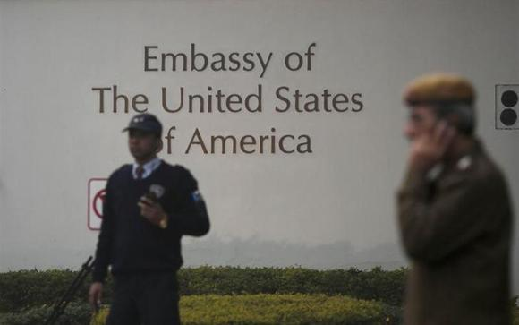 A U.S. embassy security guard (L) and an Indian policeman stand in front of the main gate of the embassy as the bulldozer (unseen) removes the security barriers, in New Delhi December 17, 2013. REUTERS/Adnan Abidi